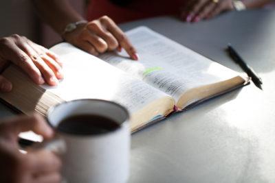 Women pointing at Bible verse