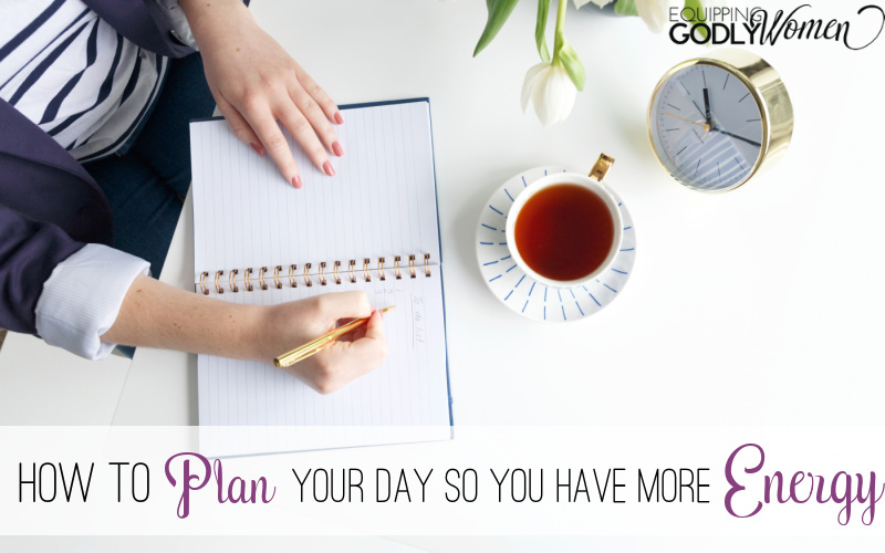 Woman planning her day writing in a planner.
